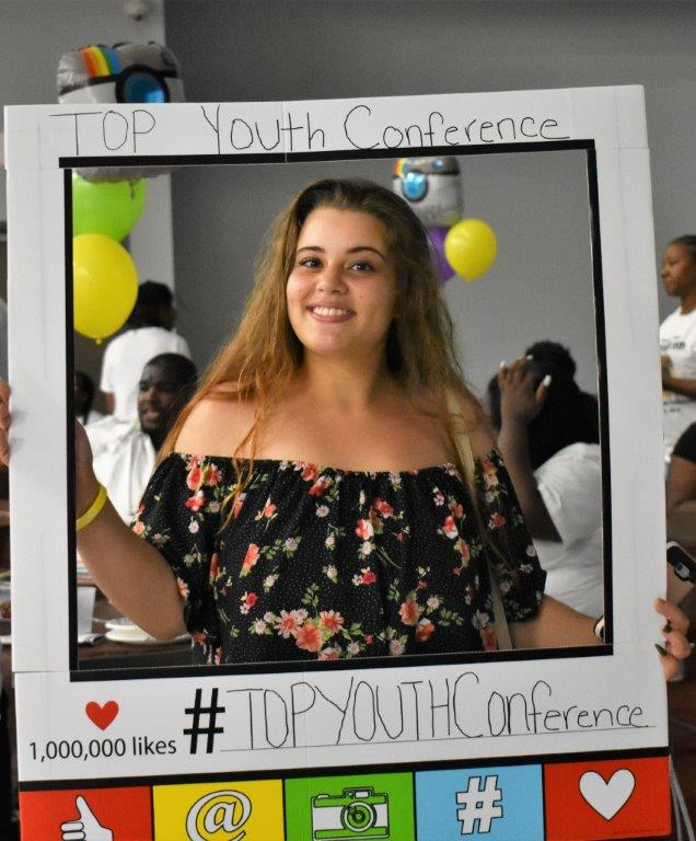 """A young person is holding a frame with the text """"TOP Youth Conference, 1,000,000 likes, #TOPYOUTHConference"""