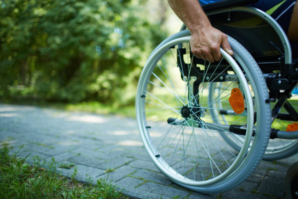 Man in a wheel chair on a stone pathway