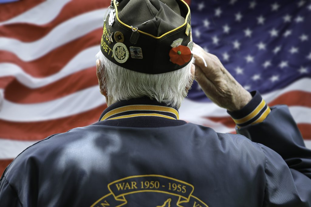 Elderly veteran man saluting the American flag