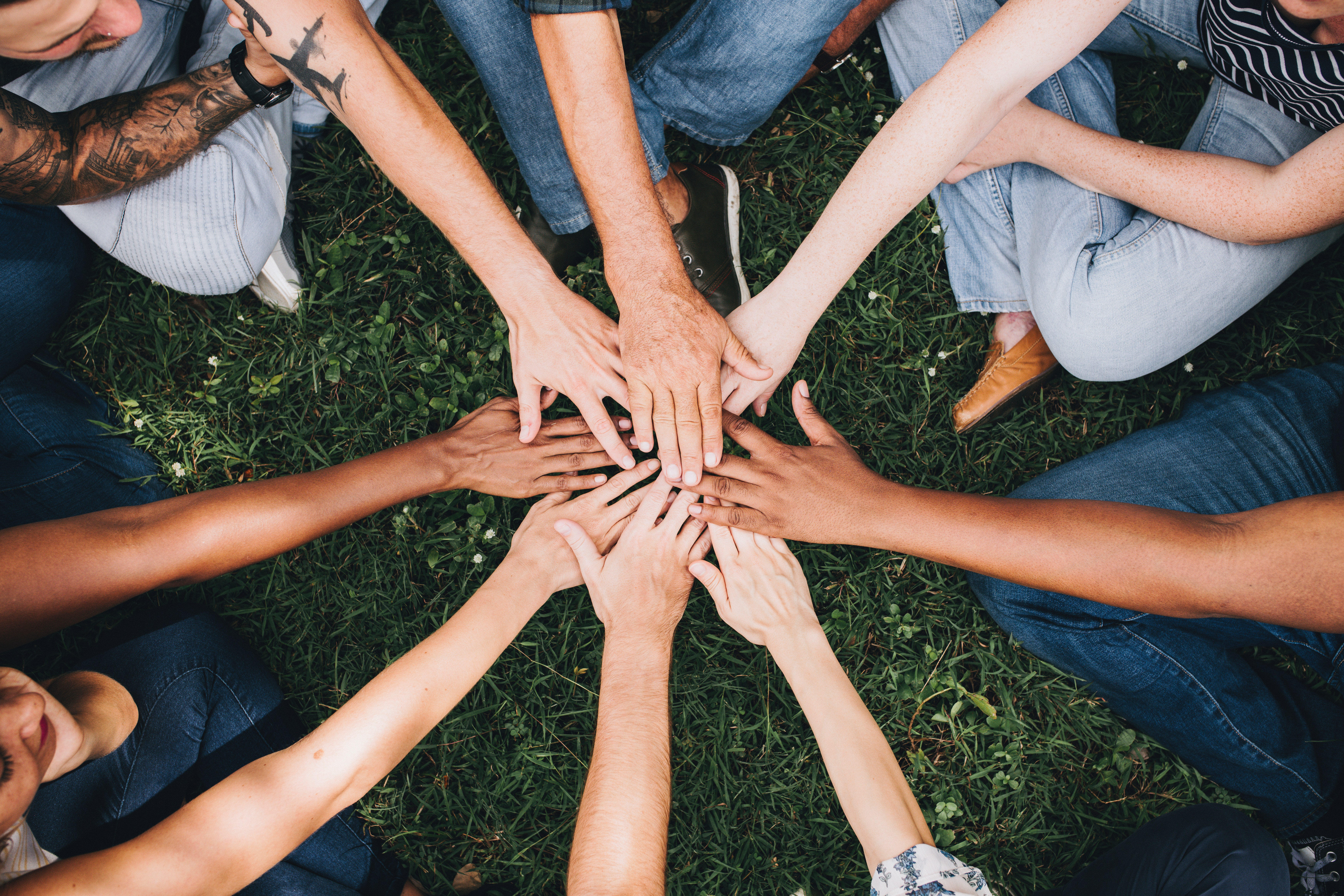 Group of diverse individuals with hands in the middle of a circle