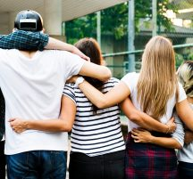 Group of young adults putting arms around each others' backs