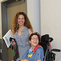Woman next to another woman in a wheelchair smiling